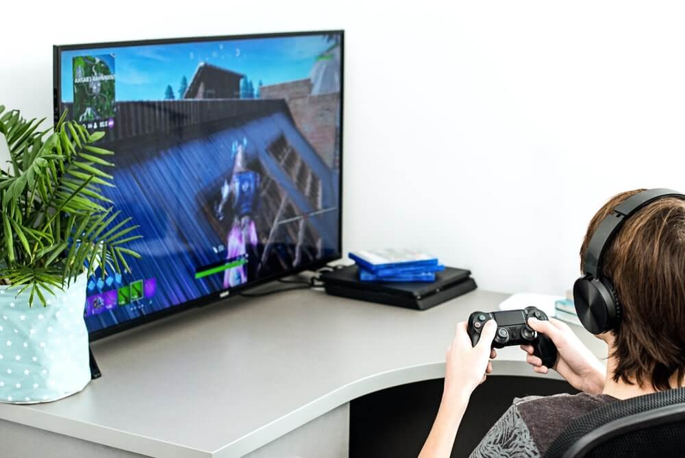 A teenager plays a fortnite computer game in headphones and with a joystick, game console, Sony Playstation 4
