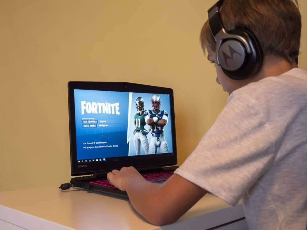 a boy playing Fornite using keyboard and mouse