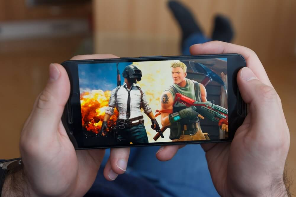 Man holding a smartphone with the Fortnite game open
