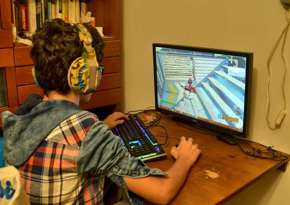 Teenager playing Fortnite on PC