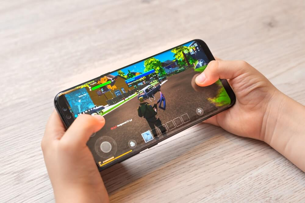 A man playing Fortnite on his smartphone